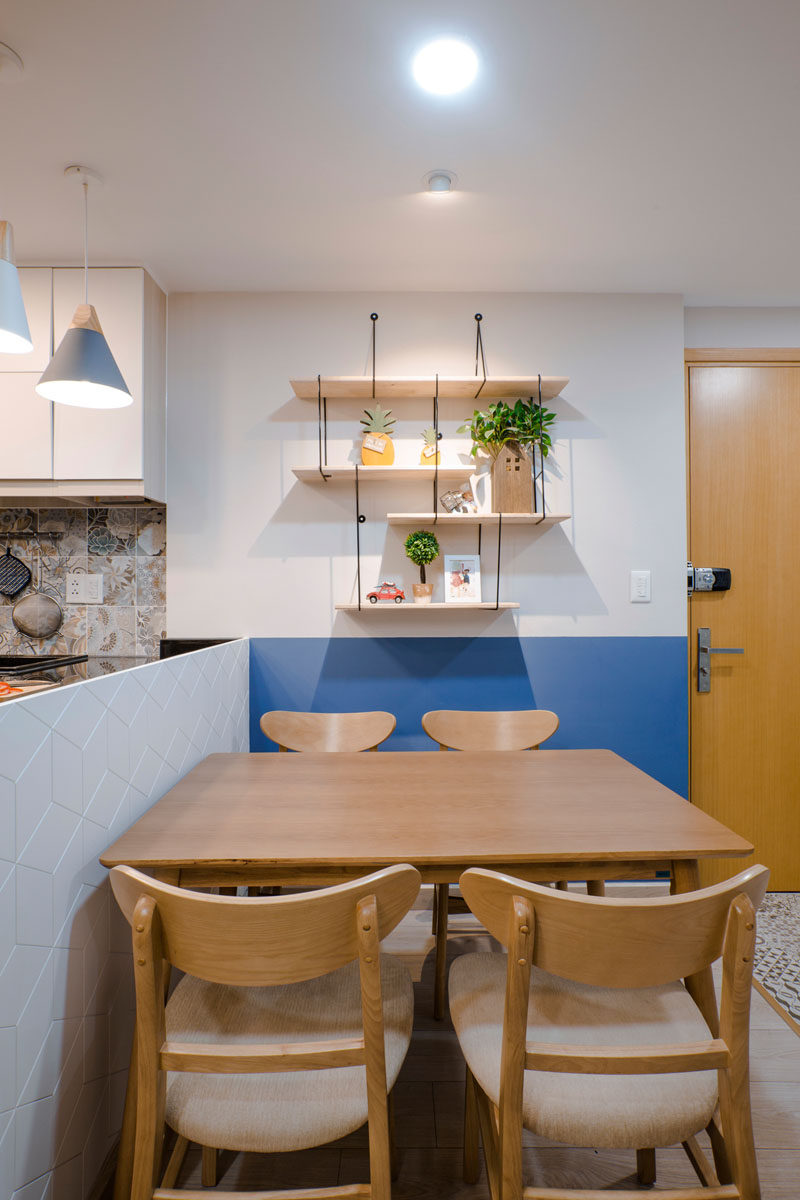 Wood shelves, decorated with plants and personal items, hang on the wall of this dining area, while a blue section of wall matches up with the line of the kitchen. Click through to see more photos of this apartment. #DiningRoom #HangingShelves