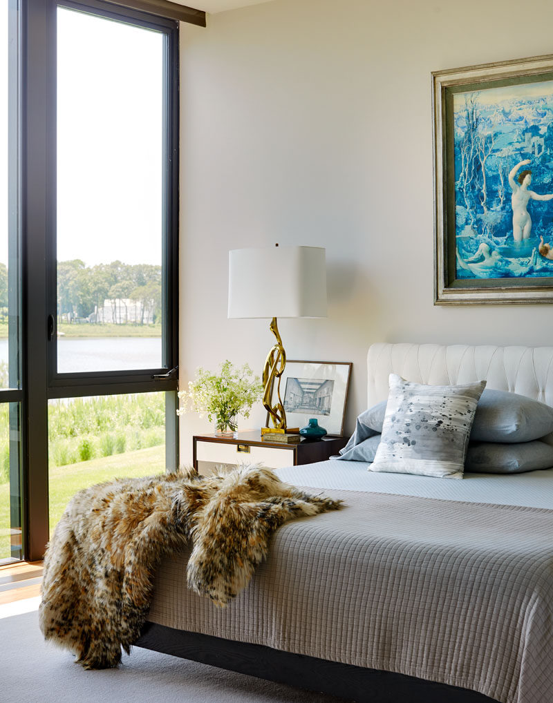 Large windows fill this contemporary bedroom with natural light and provide views of the harbor and cove in the distance. #Bedroom #BedroomIdeas #BedroomDesign