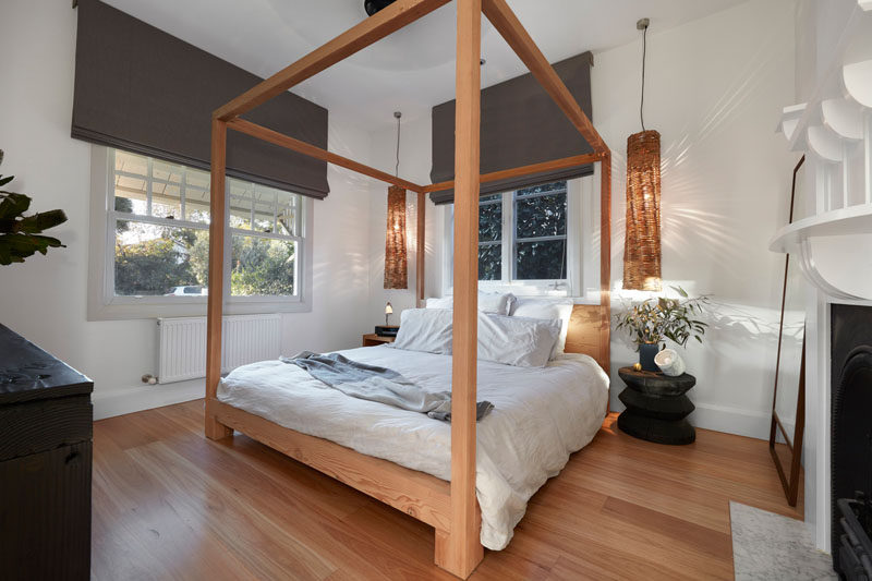 A simple four post wooden bed frame matches the wood flooring in this contemporary bedroom. #BedroomDesign #InteriorDesign