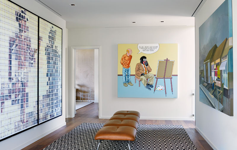 A hallway that connects the bedrooms in this modern house is lined with the home owners art collection. #ModernHallway #Gallery #InteriorDesign