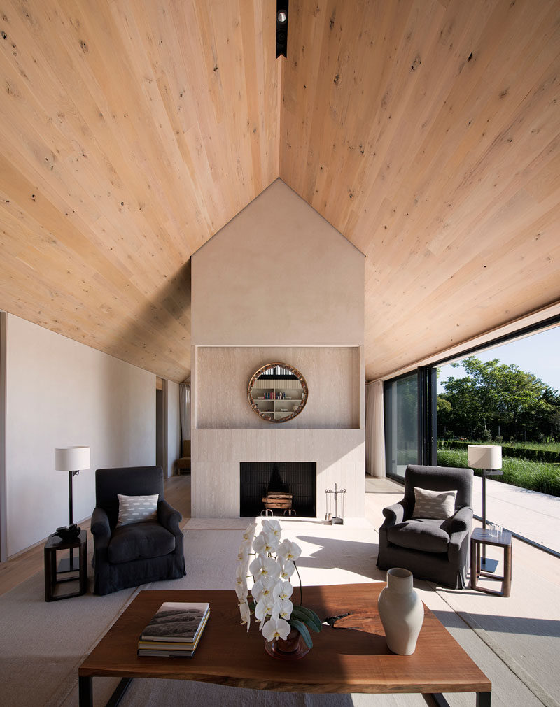 Inside this modern house, wood covers the ceiling and oak has been used for the floor, while sliding glass doors open the interior spaces to the patio outside. #ContemporaryLivingRoom #WoodCeiling #Fireplace #InteriorDesign