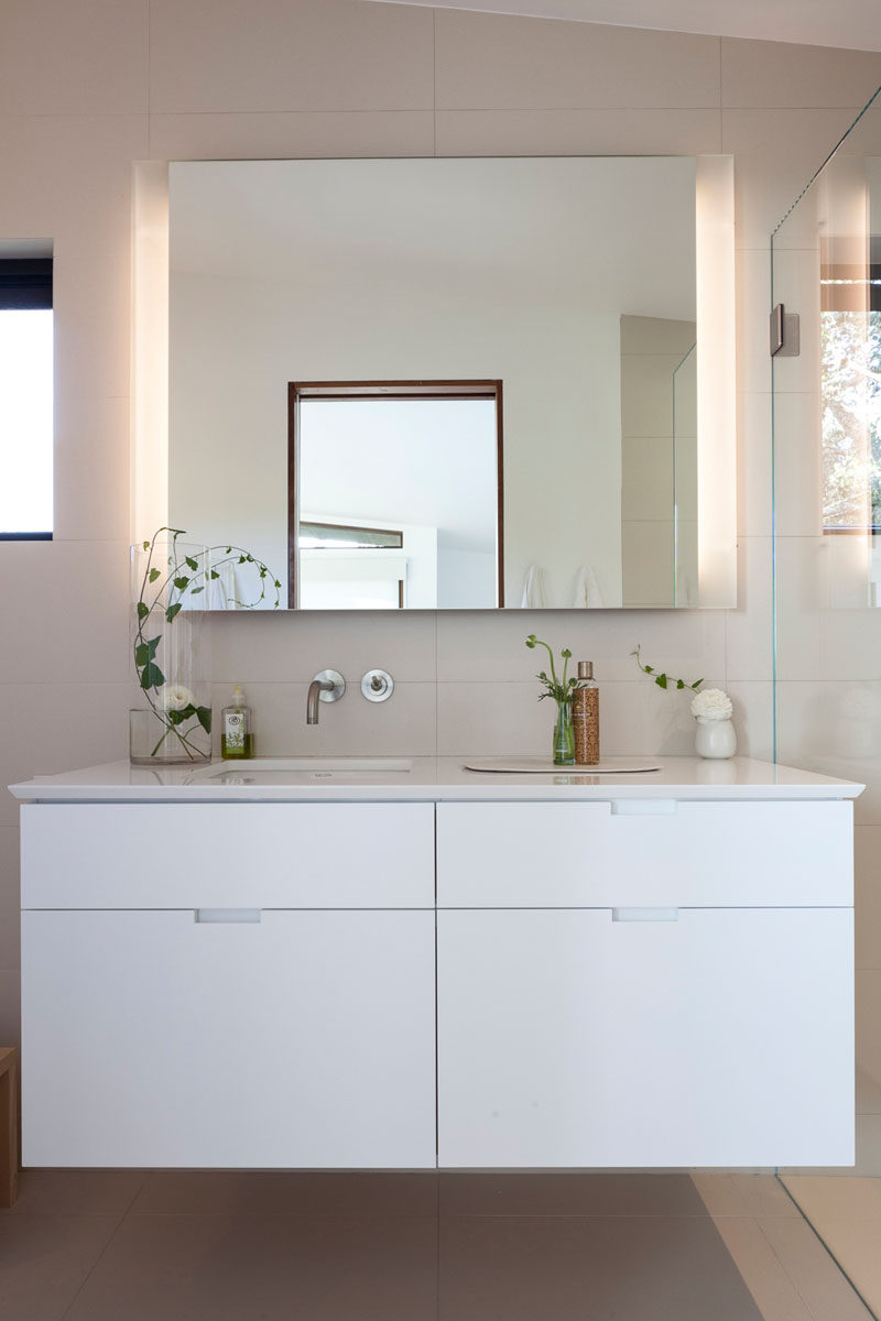 This contemporary bathroom has been kept bright with the use of light porcelain tiles and a white vanity. #BathroomDesign #Bathroom