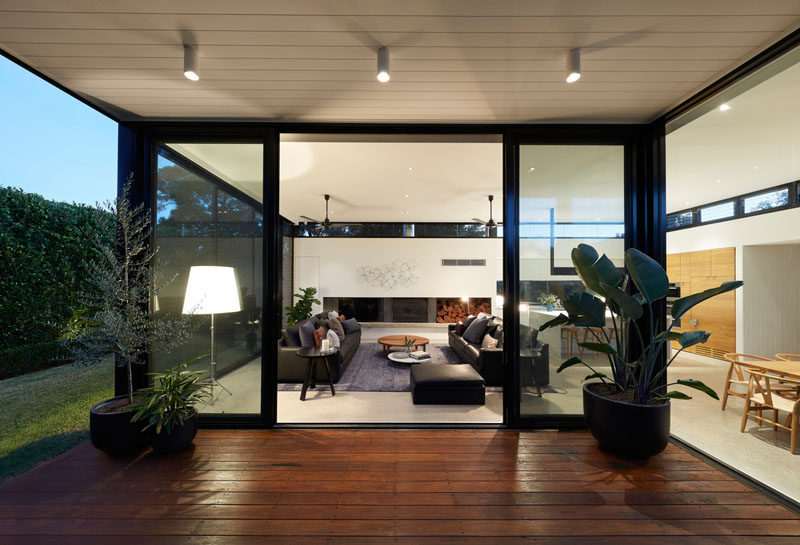Sliding glass doors open this modern living room to a covered patio for outdoor dining. #Patio #LivingRoom #ModernHouse