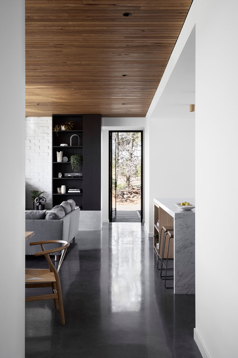 This modern house interior features a Blackbutt shiplap ceiling and burnished concrete flooring. #ConcreteFloor #DarkConcreteFloor #Flooring #WoodCeiling #Shiplap #ModernInterior
