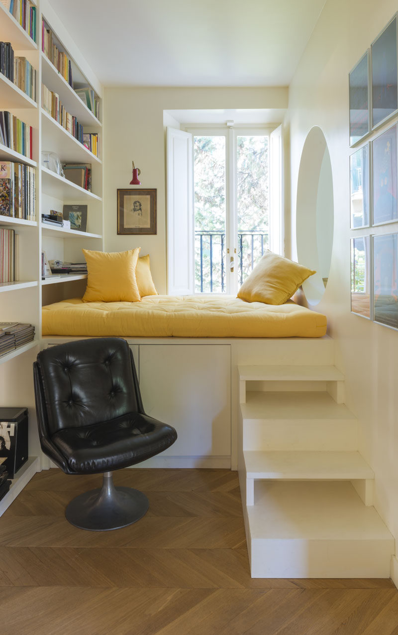 This modern home features an elevated reading nook that sits next to a window and a floor-to-ceiling bookshelf, and that has an opening that looks into the living room. #ReadingNook #InteriorDesign #CozyNook #Nook