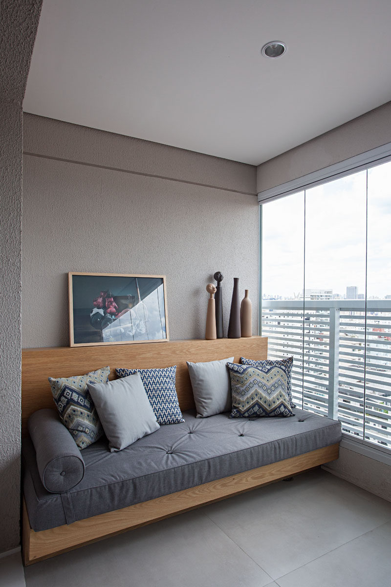 This partially enclosed balcony has a wood couch/day bed with a small ledge for displaying personal items. #Couch #Balcony #DayBed