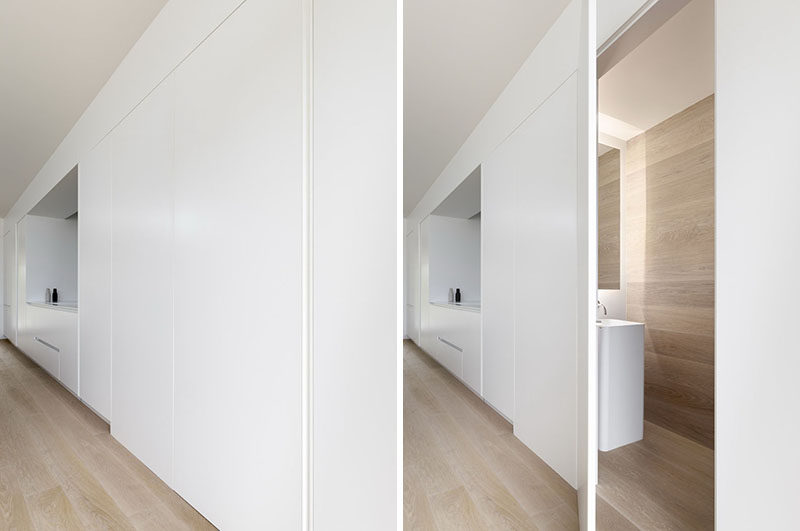The streamlined minimalist white kitchen cabinets line the wall in this modern house, and hidden behind one door is a powder room. #HiddenPowderRoom #KitchenDesign #WhiteCabinets