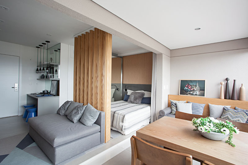 The modern living and sleeping areas of this small apartment open up to an integrated balcony that has a living area, dining area and laundry space. #SmallApartment #InteriorDesign #IntegratedBalcony #WoodSlatPartition #WoodSlatWall