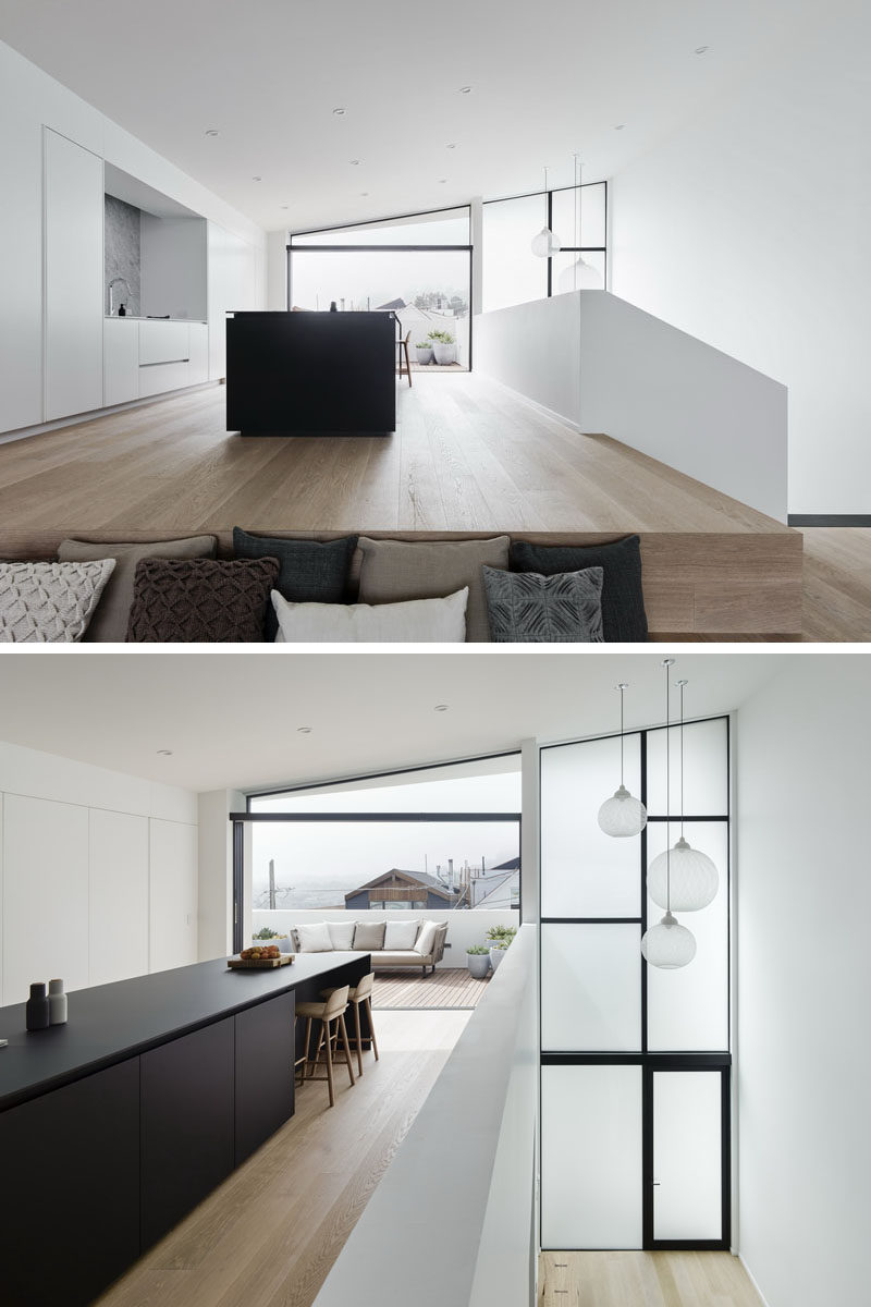 As the kitchen in this modern house is open to the stairwell,the architects made guardrails from simple drywall, keeping in line with the modern aesthetic of the house. #ModernKitchen #BlackKitchenIsland #Windows