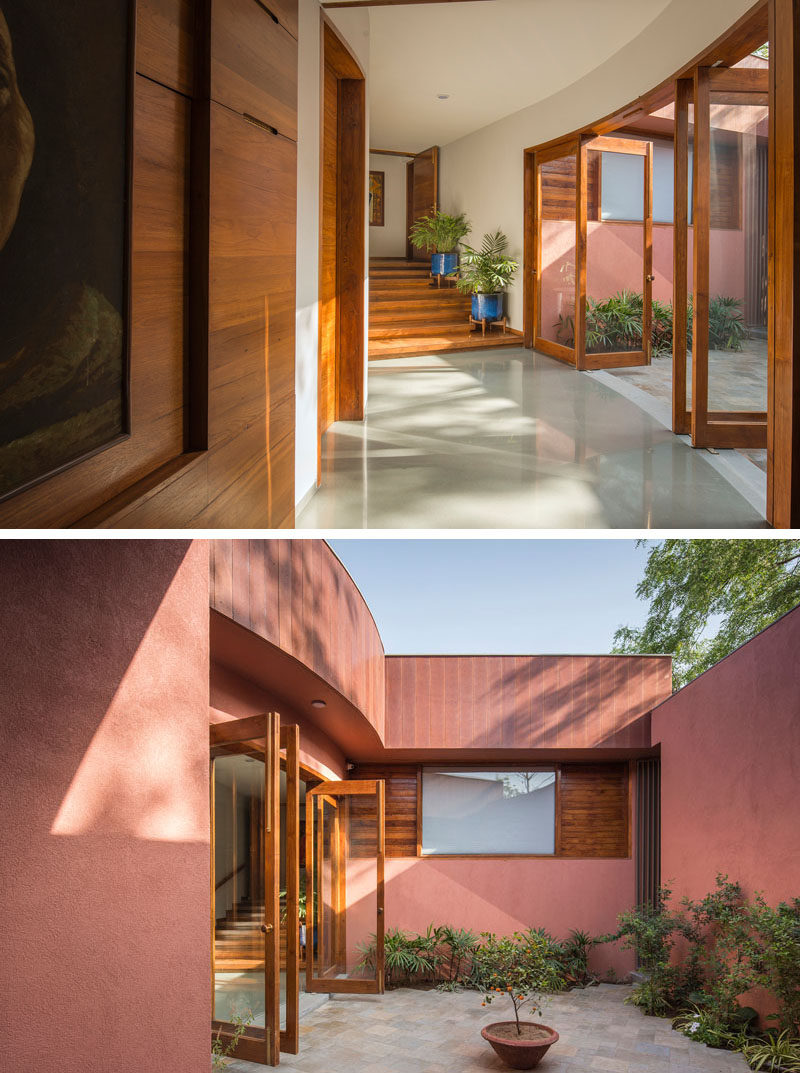 Located just off a curved hallway in this contemporary house, is a small private courtyard with a patio and plants. #Courtyard #Hallway #Doors