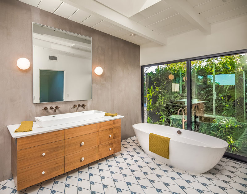 In this ensuite bathroom, there's a standalone bathtub that takes advantage of the large floor-to-ceiling windows, and has a view of a lush garden. #Bathroom #Ensuite #WoodVanity #Windows #StandaloneBathtub