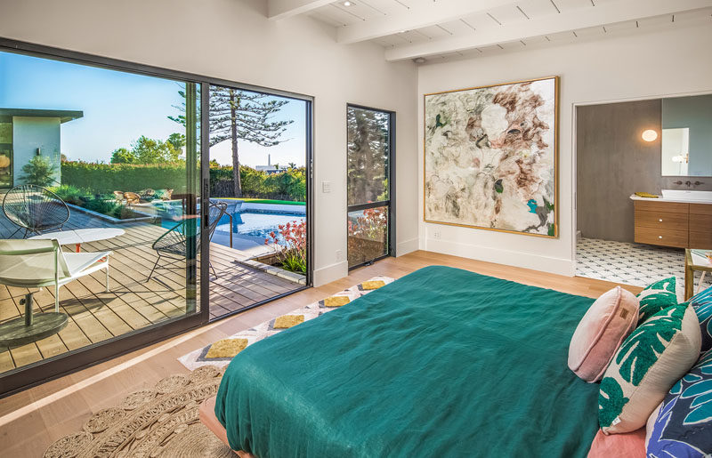 This modern master bedroom has a sliding door that opens to the deck and an ensuite bathroom.