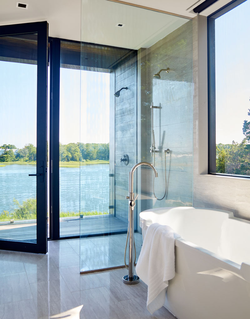 This modern bathroom has floor-to-ceiling windows and glass door that opens to a small balcony. #ModernBathroom #BathroomDesign