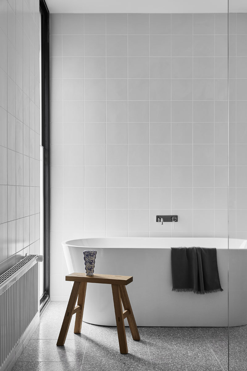 Square tiles have been used to cover the walls in this bathroom, while a freestanding white bathtub is positioned to take advantage of the views out of the window. #ModernBathroom #SquareTiles #FreestandingBathTub