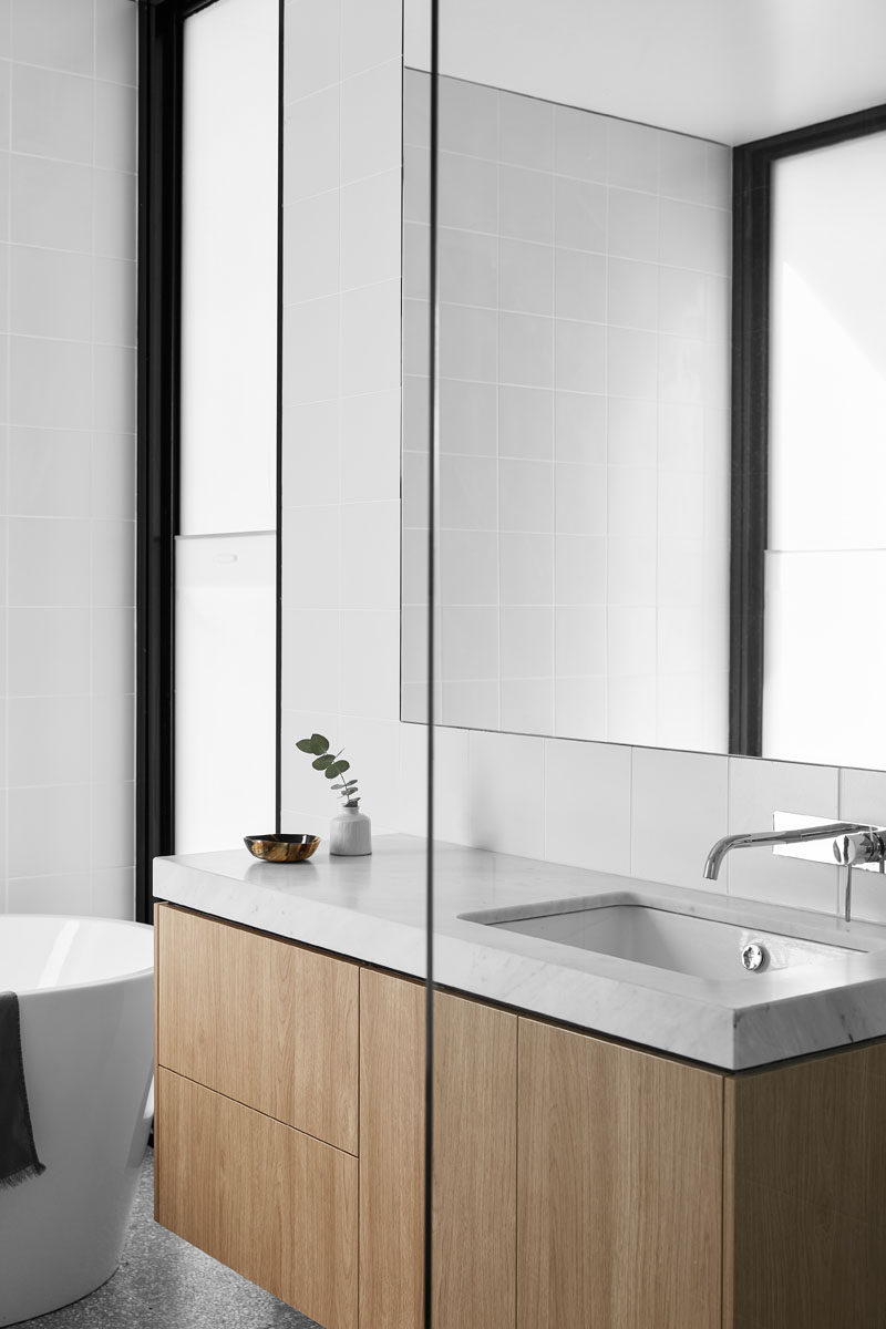 In this modern bathroom, a wood vanity adds a natural touch to the mostly white space. #ModernBathroom #WoodVanity