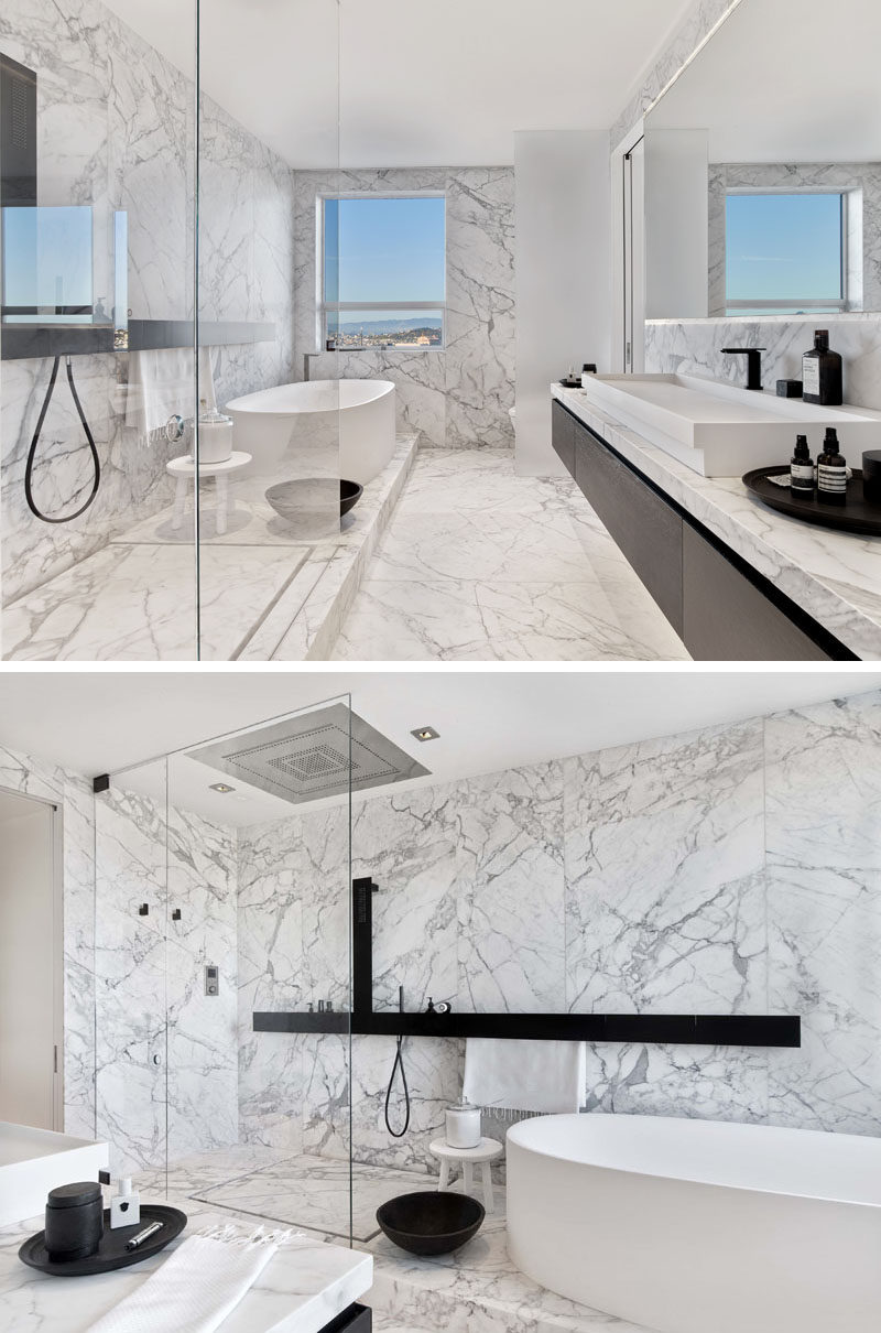 This modern master bathroom has floors and walls of carefully selected and matched Carrara marble slabs that are contrasted with dark fixtures to evoke the feeling of being in a spa. #ModernBathroom #MarbleBathroom #WhiteBathroom #InteriorDesign