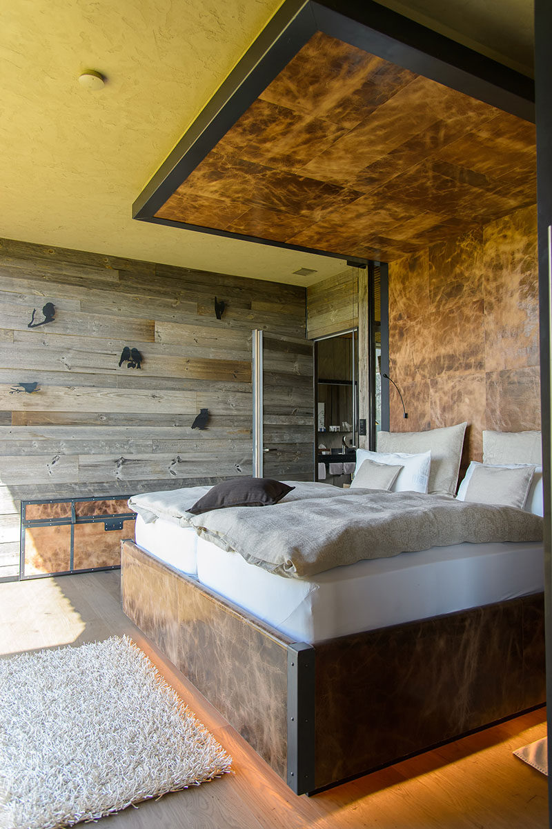 This modern mountain chalet has a bed frame wraps around the bed to become the headboard, that then continues onto the ceiling, creating a dramatic accent in the bedroom. #Bedroom #Bed #Headboard #Wood