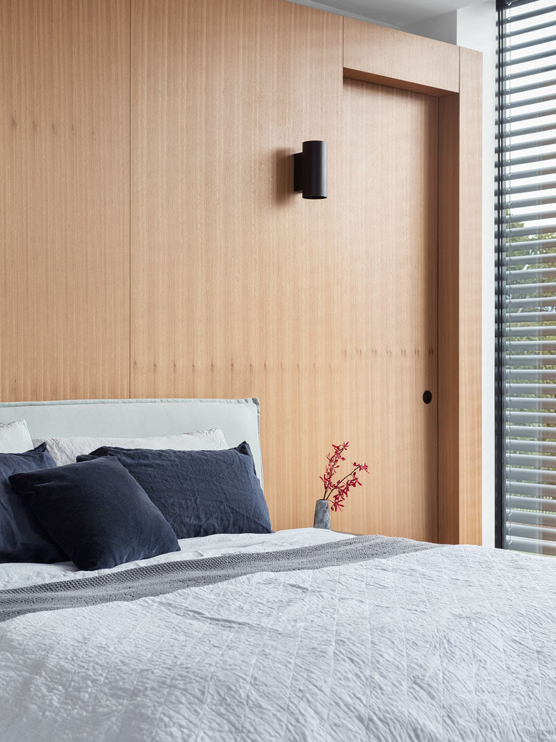 This modern bedroom has an wood accent wall with doors that open to closets. #ModernBedroom #WoodAccentWall