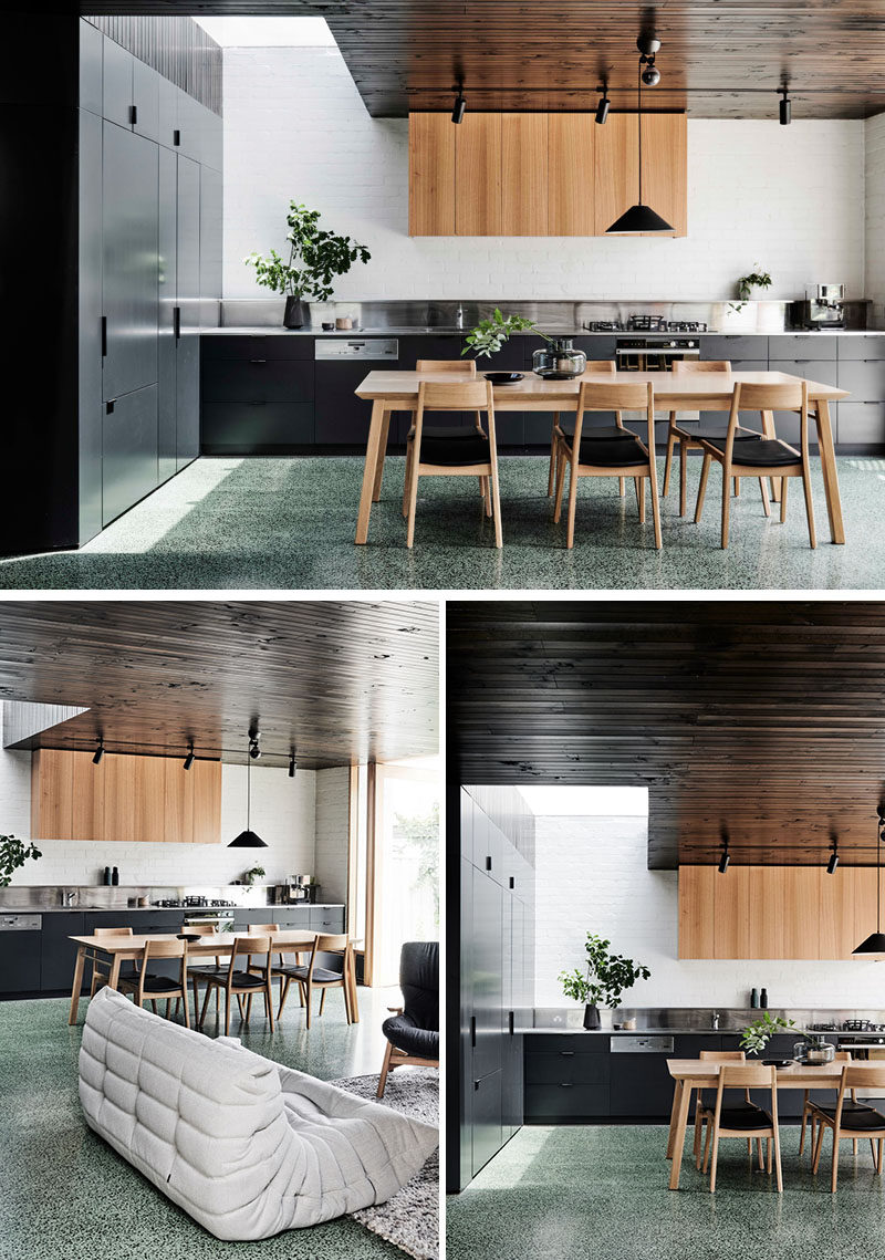 In this modern kitchen, appliances like the fridge are hidden in plain sight within the dark cabinets, and a stainless steel backsplash helps to reflect light. #ModernKitchen #KitchenDesign #InteriorDesign