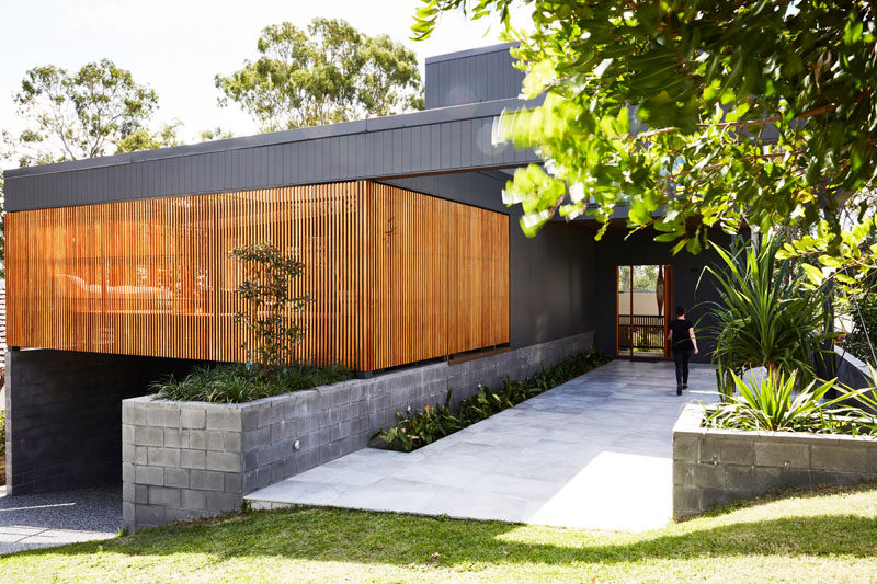 This modern black house has a wood slat detail that hides a private patio. #ModernHouse #ModernArchitecture