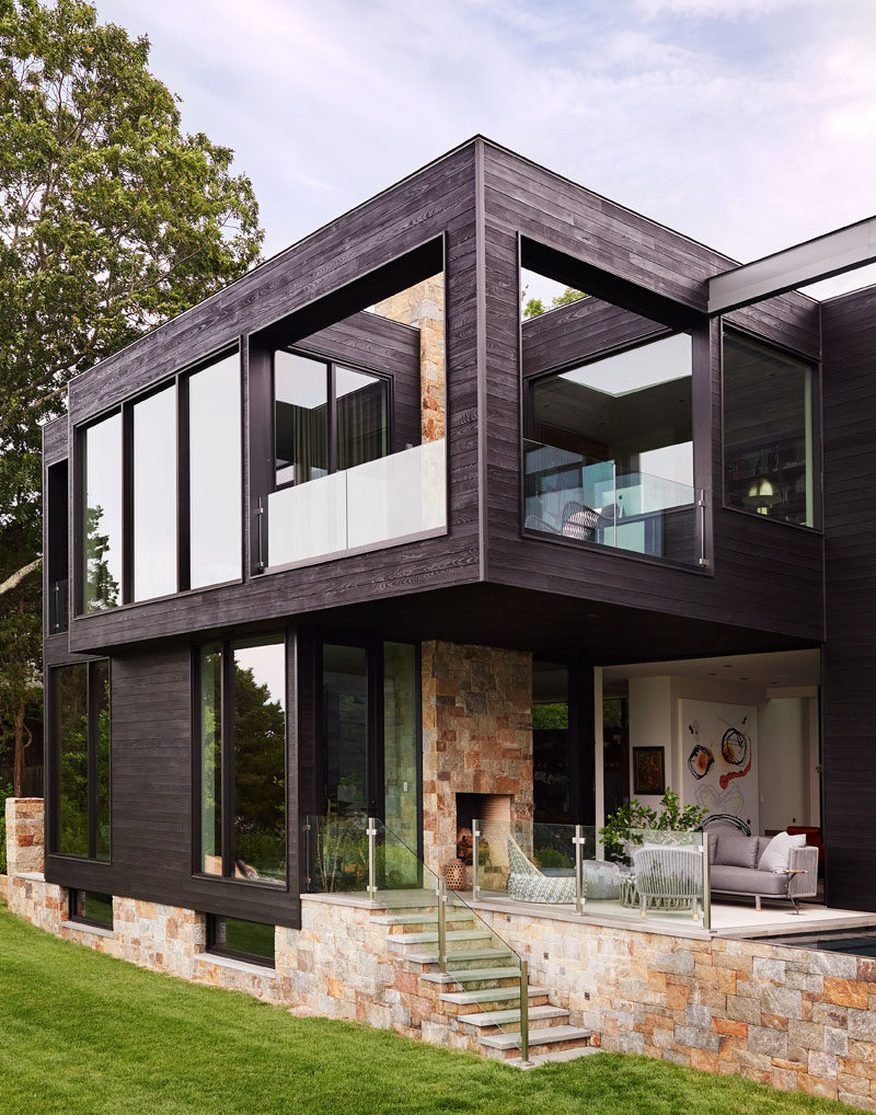 This modern house has a small outdoor lounge with a fireplace and steps that lead down to the lawn.#OutdoorLounge #OutdoorFireplace #Stone