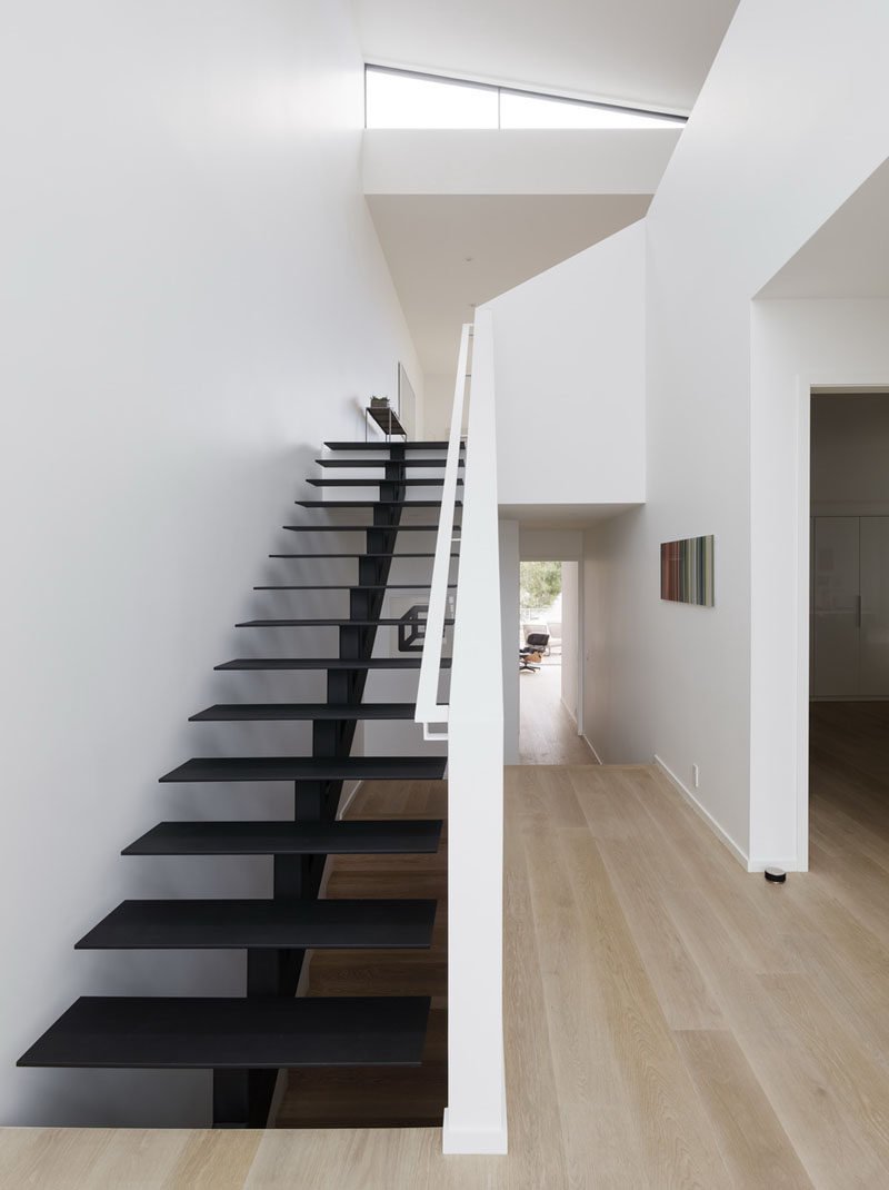 Minimalist black painted steel stairs lead to the upper floor of this modern house. #ModernStairs #BlackStairs
