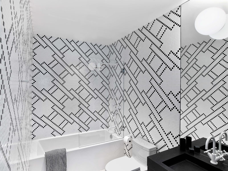 In this modern bathroom, the color palette has been kept simple by using black and white tiles, paired with a white bathtub and a black vanity. #BlackAndWhite #BathroomDesign #ModernBathroom #Pattern