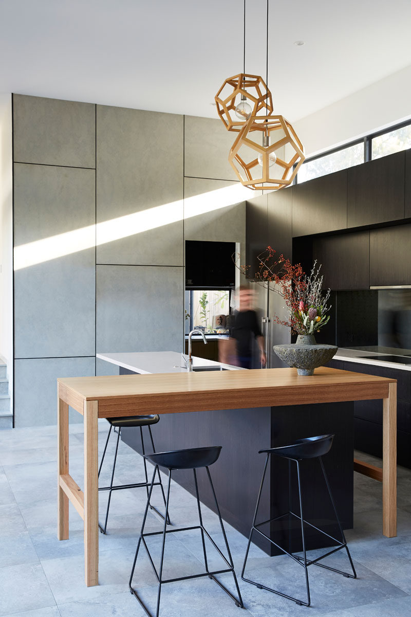 In this modern kitchen, black cabinets have been combined with wood elements and white countertops. #ModernKitchen #KitchenDesign
