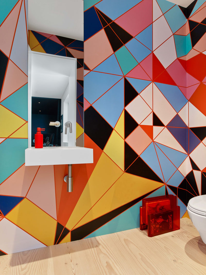 This modern bathroom has colorful and bold geometric pattern that covers the wall. #BrightBathroom #ColorfulBathroom #BathroomDesign