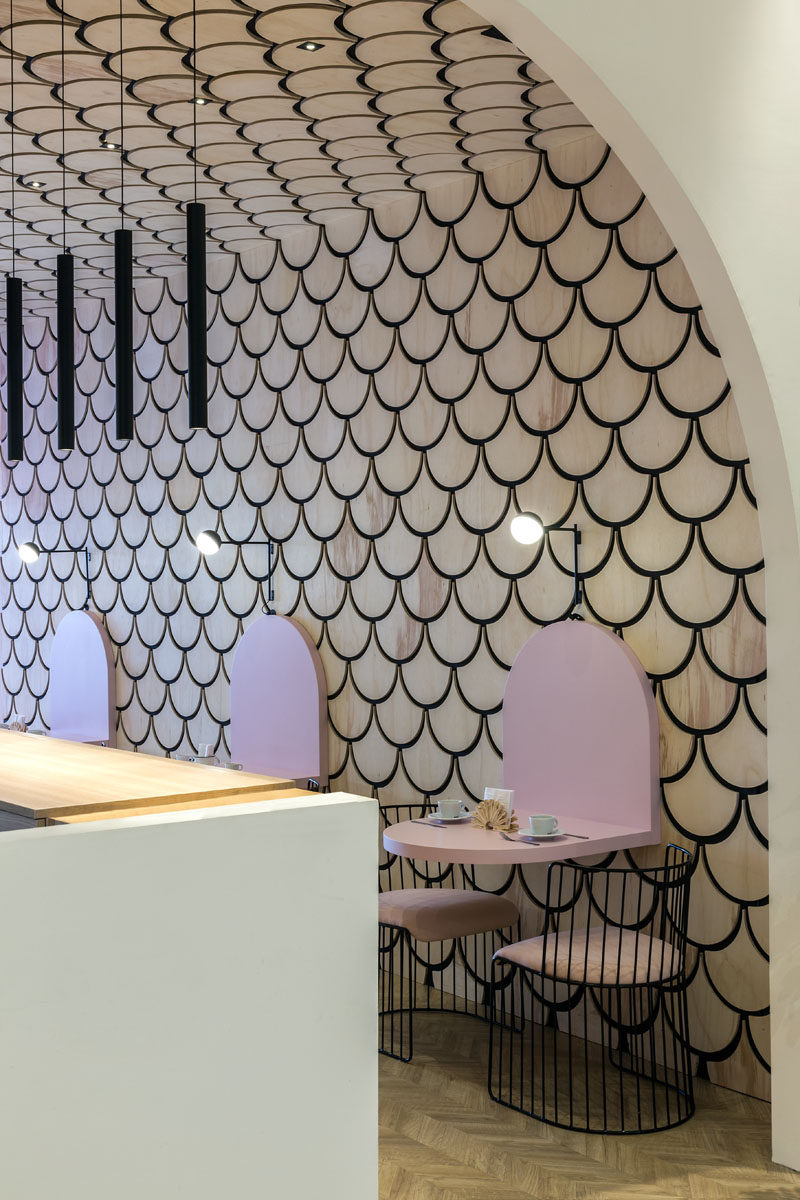 This modern patisserie features a scalloped or fish scale patterned wood accent wall. #ModernPatisserie #CafeDesign #InteriorDesign #Cafe #AccentWall