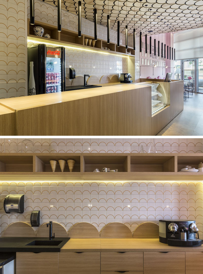 In this modern patisserie, hidden lighting under the mounted wall shelf and a line of individual pendant lights above the service area, help to keep the space bright. #ModernCafe #ModernPatisserie #InteriorDesign