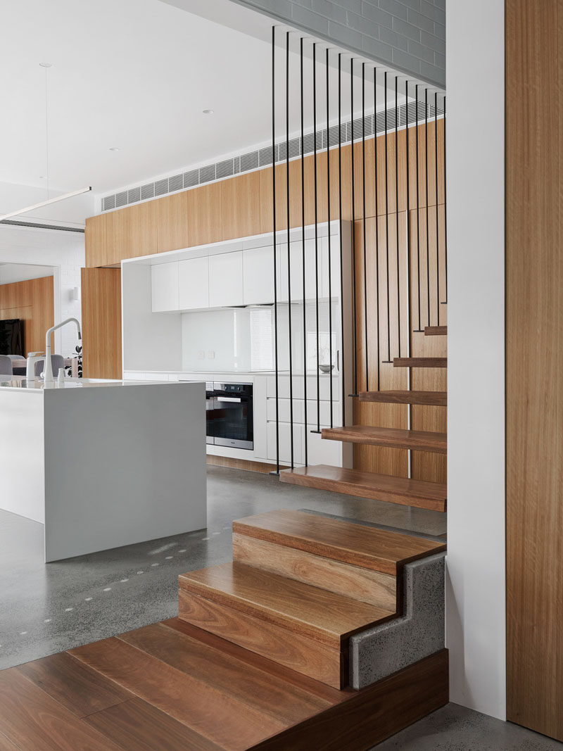 This modern house features modern concrete, steel and wood stairs that lead to the upper floor of the home. #ModernStairs #WoodStairs #StairDesign