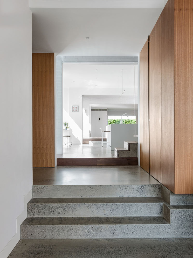 This modern house features polished concrete flooring, wood cabinetry and accents, and bright white walls. #ModernHouse #ConcreteFlooring #WhiteWalls #WoodCabinetry