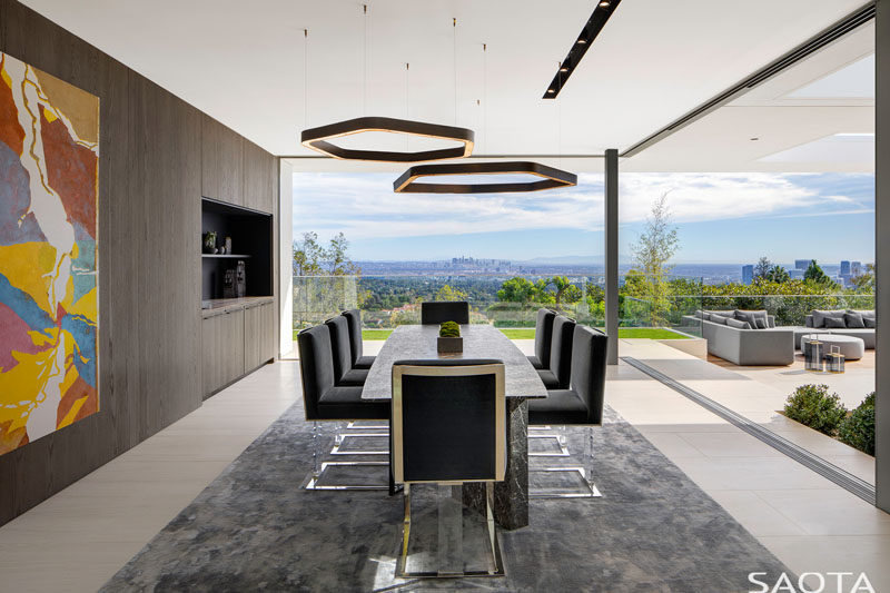 Where possible, walls in this renovated home were replaced by full height glazing with sliding windows, pocketing or stacking, to create generous openings, like in this dining room. #ModernDiningRoom #GlassWalls #InteriorDesign