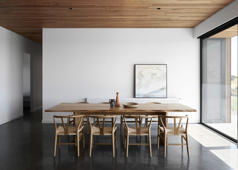 This dining room features a burnished concrete floor and a Blackbutt shiplap ceiling. #Shiplap #DiningRoom #ConcreteFloor