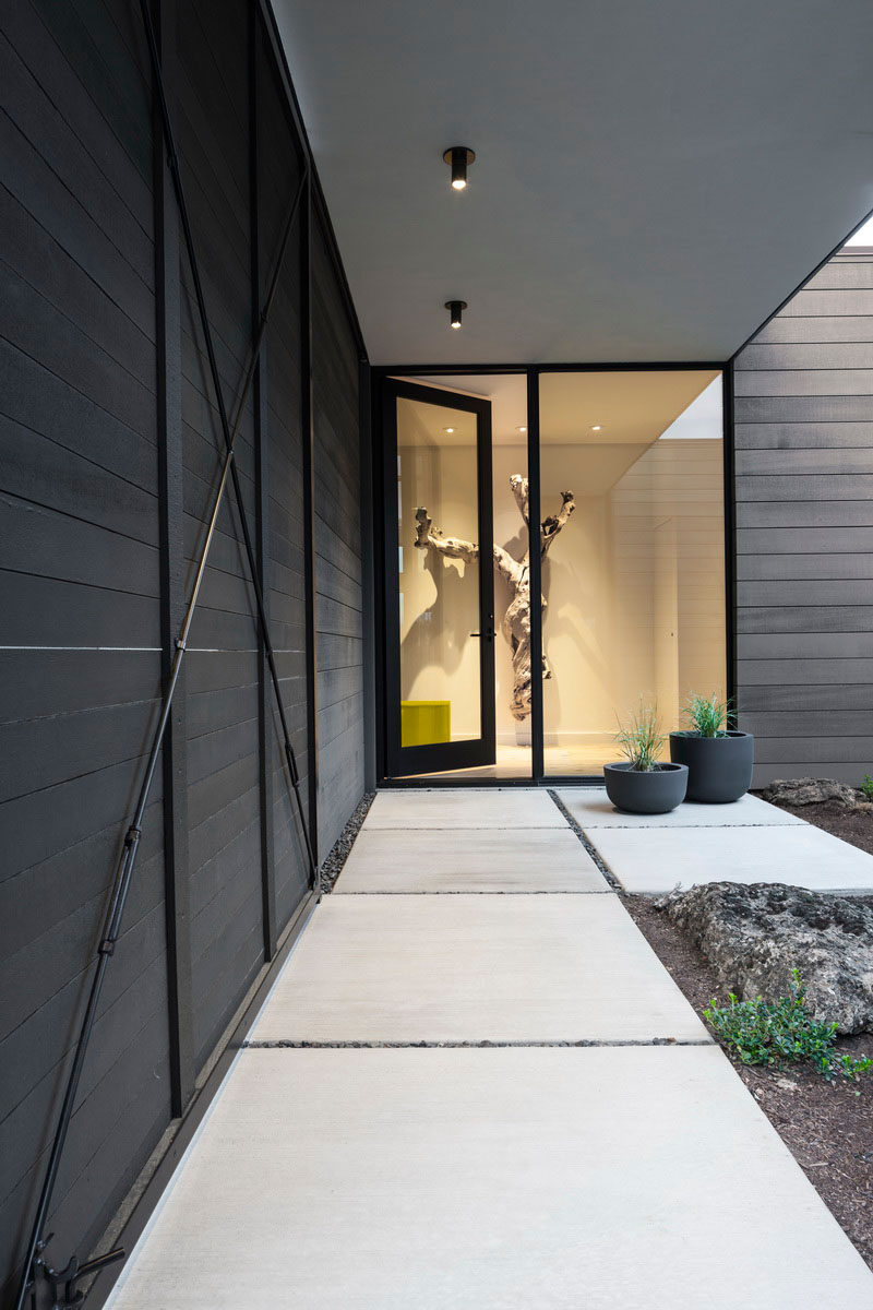 At the entry courtyard of this modern house, a rolling screen and swinging gate can be configured to be cozy and private, or wide open and welcoming. #ModernHouse #GlassDoor #ConcretePath
