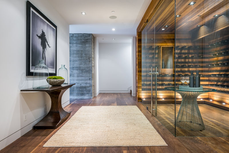 This modern house has a glass enclosed wine cellar with plenty of shelving and uplighting for showing off a wine collection. #WineCellar #WineStorage #InteriorDesign