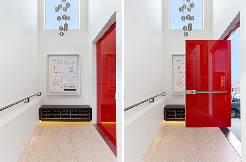 A bright red, glossy pivoting door that was fabricated in Italy, welcomes visitors to this modern house. #RedFrontDoor #FrontDoor #ModernHouse #Entryway