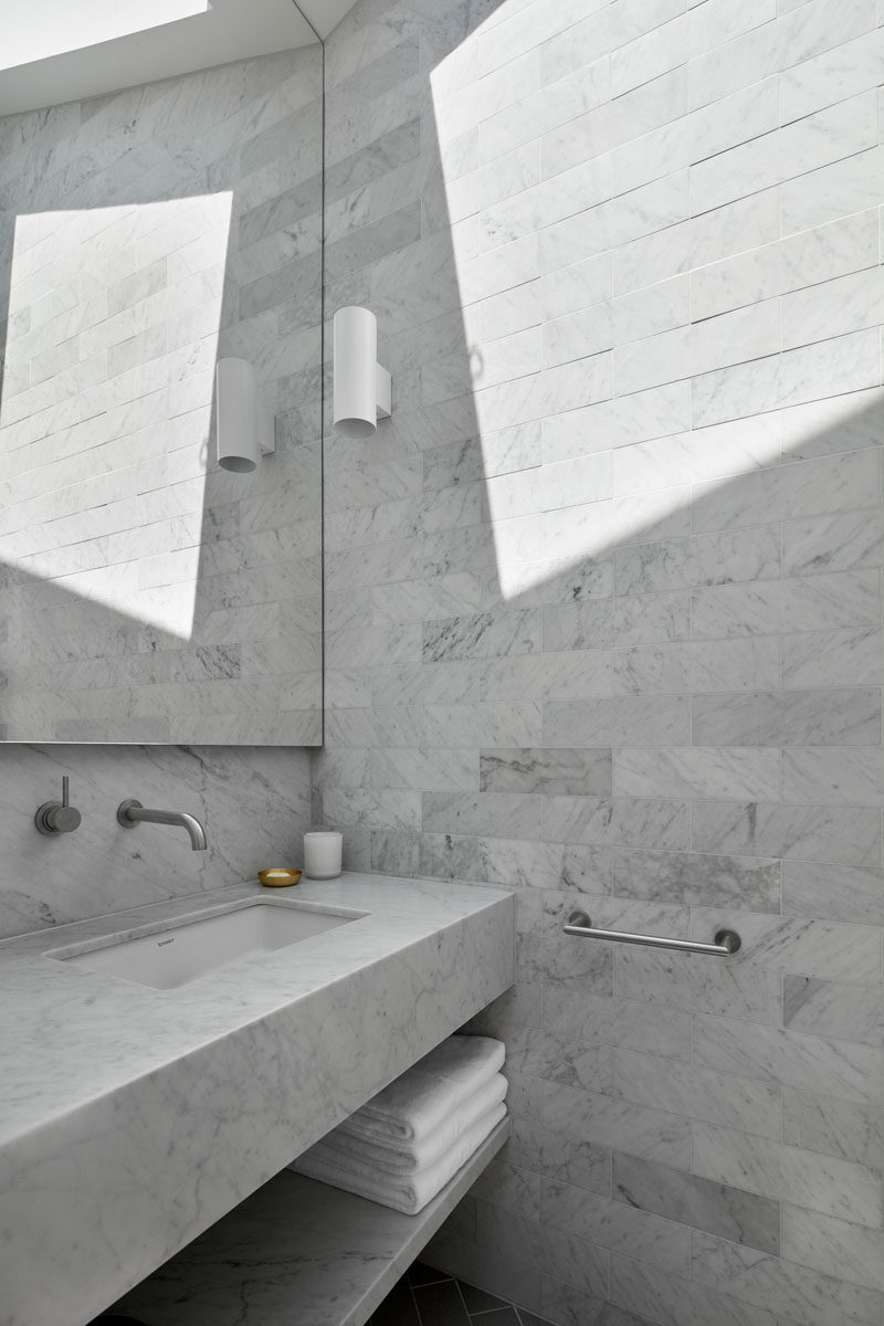 Floor-to-ceiling grey tiles have been installed in this new bathroom, and a skylight adds natural light to the room. #ModernBathroom #Skylight #BathroomDesign #GreyTiles