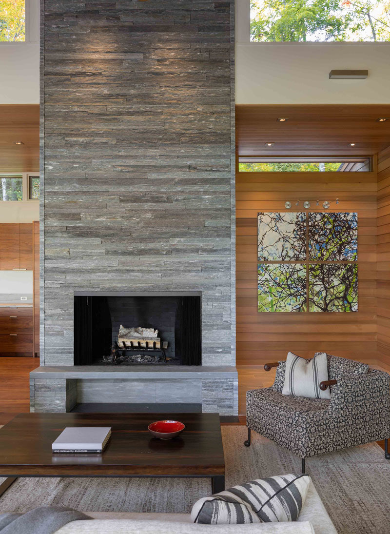 In this modern living room, there's a stacked stone fireplace and hearth, that draws the eye upwards to the clerestory windows and the height of the room. #Fireplace #StackedStoneFireplace #StoneFireplace #ModernFireplace