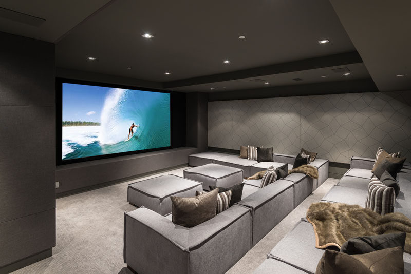 This modern house has a state-of-the-art home theater with comfortable stadium seating. #HomeTheater #MovieRoom #InteriorDesign