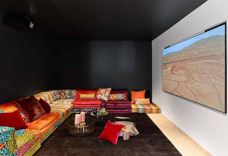 This modern house has a media lounge with black walls and a black ceiling, creating a cave-like atmosphere to enjoy the movie. #HomeTheater #MovieRoom