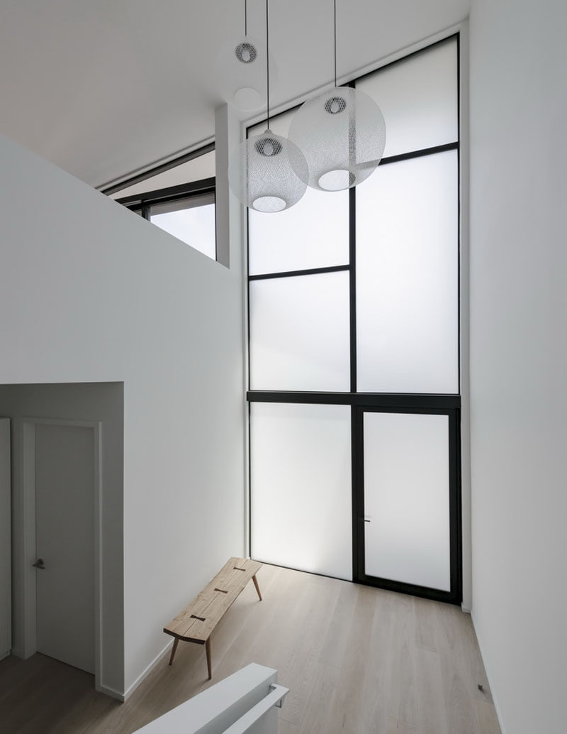 This house features tall frosted windows in the foyer that provide privacy from the street and still enable the natural light to travel inside. #Windows #FrostedGlass #Foyer #Entryway #Minimalist