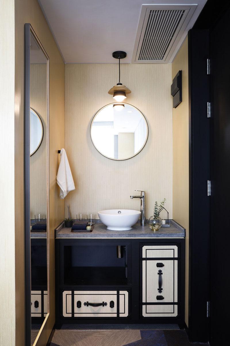 This modern hotel bathroom features a black vanity with a concrete countertop and a simple round mirror. #HotelBathroom #BathroomInspiration #BathroomIdea #ModernBathroom