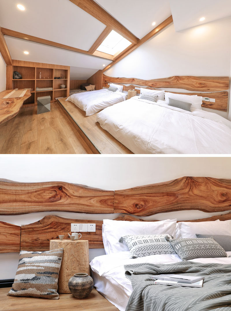 Live edge wood headboard have been mounted to the wall behind the beds in this hotel room, and the beds sit on a raised platform, creating a separation from the rest of the room. #HotelRoom #LiveEdgeHeadboard #WoodHeadboard #BedroomIdeas