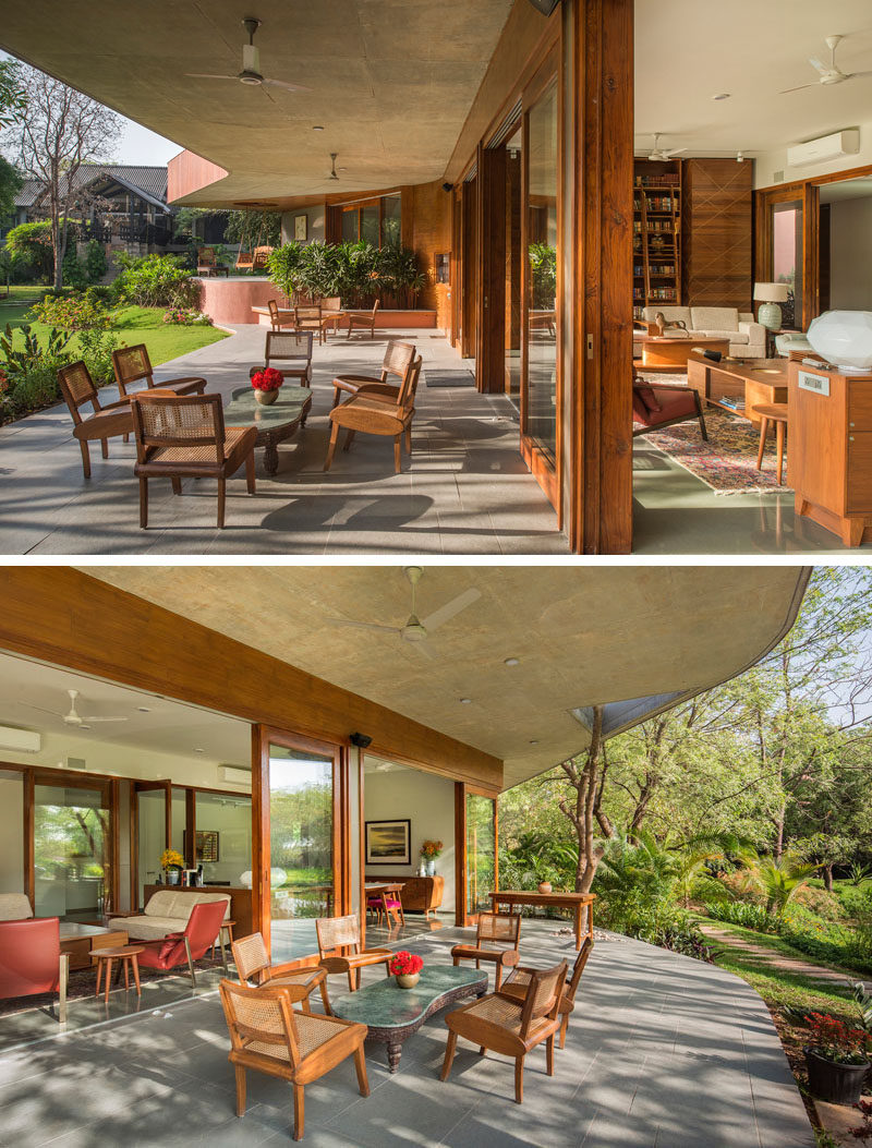 Running along the length of this contemporary house is a covered patio, set up with multiple different areas for relaxing. #Patio #HouseDesign #OutdoorSpaces