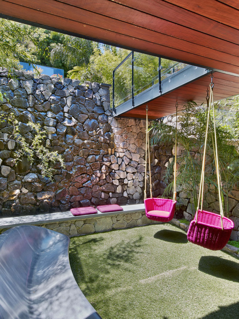 This modern house has a small grassy area with swings that hang from the bridge above, while a stone and concrete bench, and a outdoor sculptural sofa provide places to relax. #Landscaping #SmallYard #RockWall
