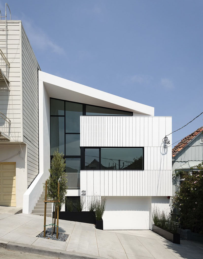 The facade of this modern house has beenbuilt from a rhythmic display of pre-manufactured trim boards. #ModernHouse #WhiteAndBlack #Architecture