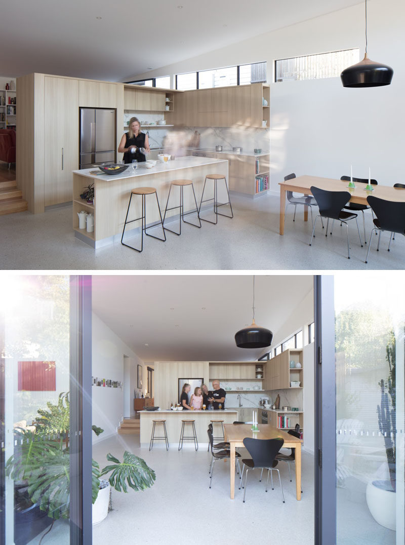 A sloped roof, a line of windows and folding glass doors that open to the backyard, allow this modern house extension to feel spacious and bright. Kitchen #LightWoodKitchen #Windows #DiningArea #InteriorDesign