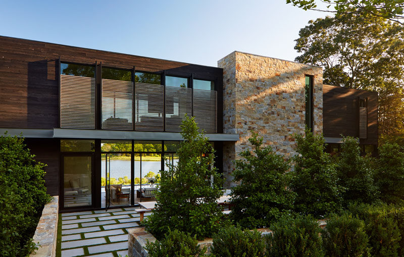 Upon arriving at this modern house, there's an patio with an outdoor dining area that's surrounded by plants. #Landscaping #ModernHouse #Architecture